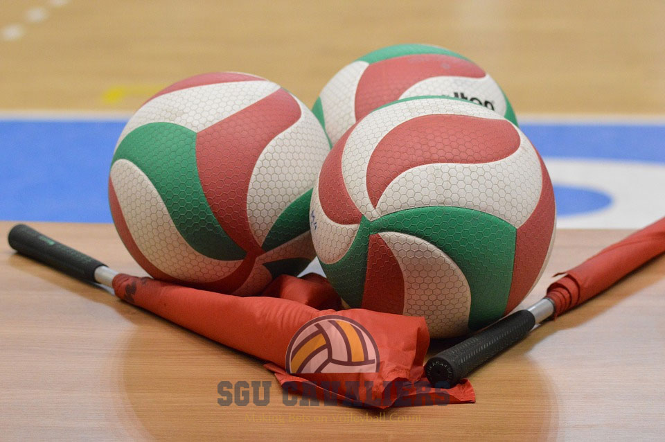 three Voleyball and a flag laying on the floor